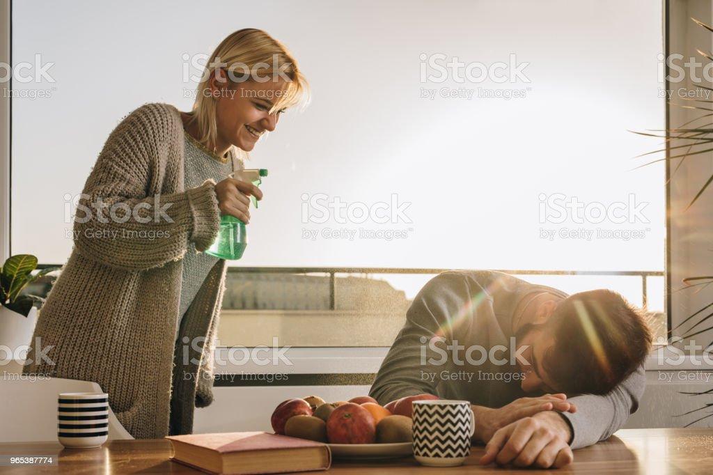 Happy woman about to wake up her boyfriend with spray bottle. zbiór zdjęć royalty-free