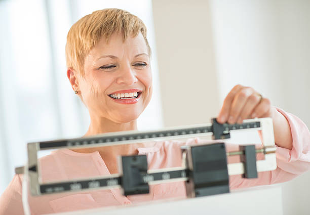 happy woman adjusting balance weight scale - scale stock photos and pictures