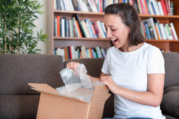Happy woman after package delivery at home stock photo