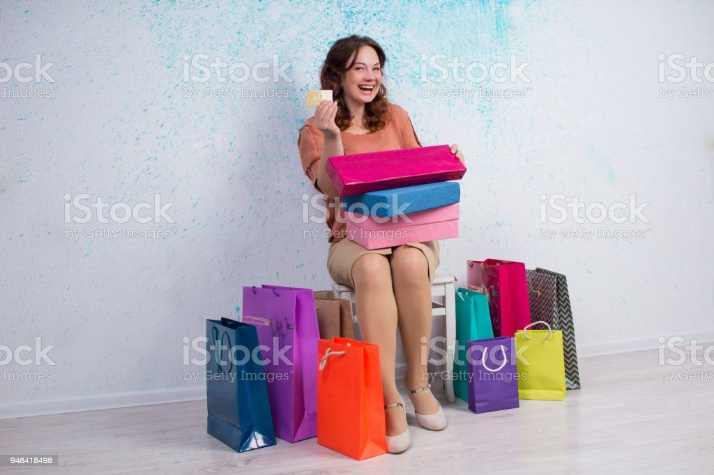 Happy woman after shopping with colorful bags, boxes, banking card stock photo
