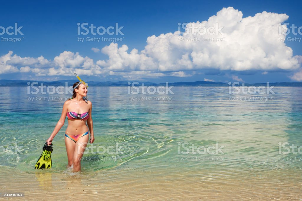 Happy woman after snorkeling with snorkel and mask coming out of the sea stock photo