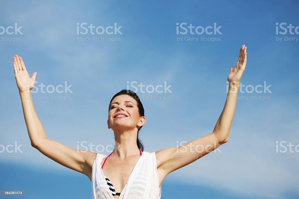 Happy woman against blue sky Summer portrait of happy woman raising her arms against blue sky. 25-29 Years Stock Photo