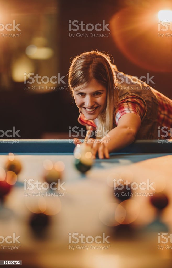 Happy woman aiming at the ball while playing billiard in a pub. stock photo