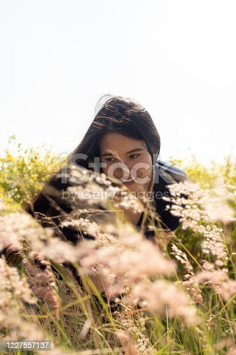 Long hair woman enjoy among wild grass in windy day and sunlight and smile.