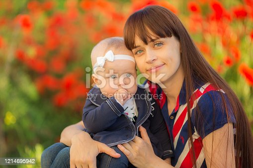 480122543 istock photo Happy woman and child on the poppy meadow. 1214695942