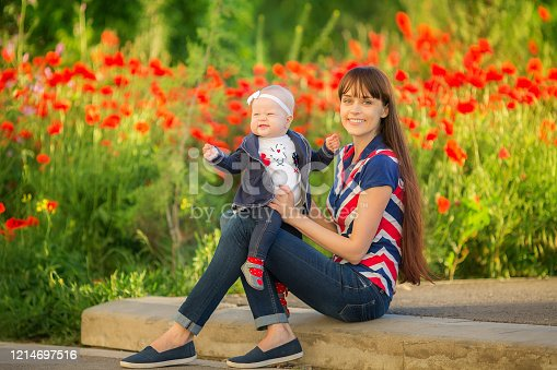 480122543 istock photo Happy woman and child on the poppy meadow. 1214697516