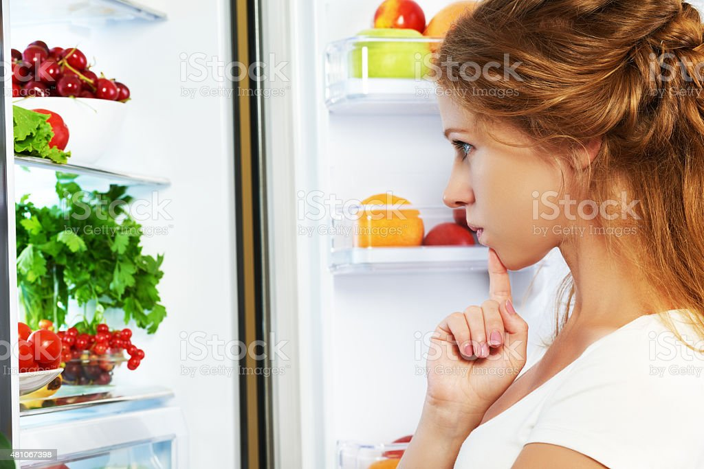 Happy woman and open refrigerator with fruits, vegetables stock photo