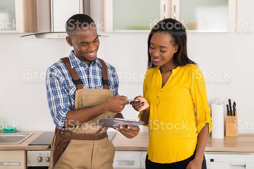 Happy Woman And Serviceman With Clipboard stock photo