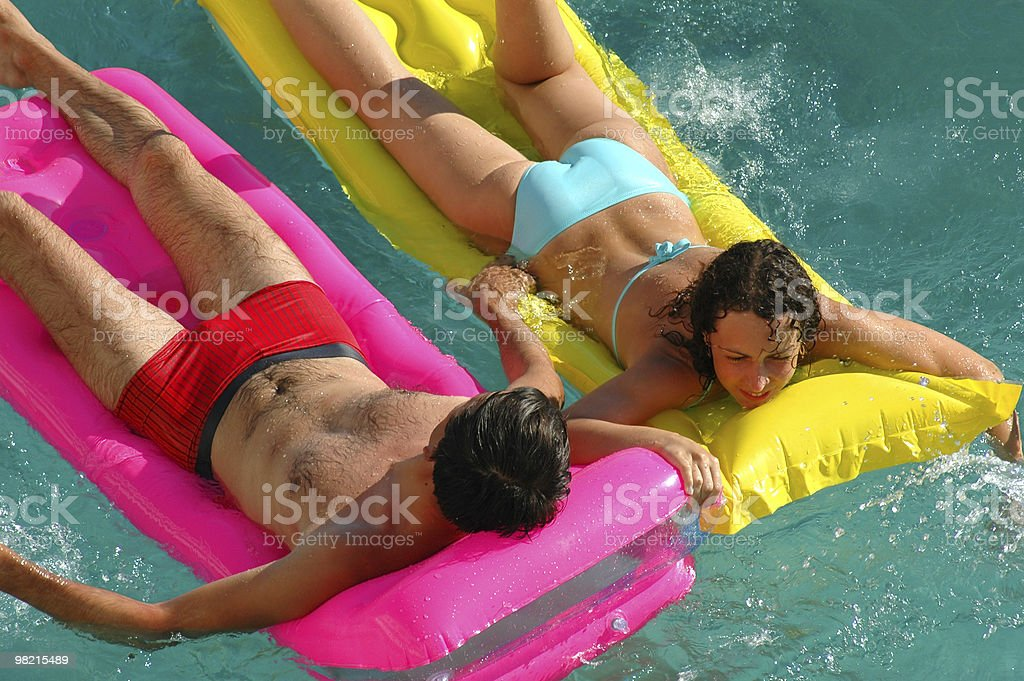 Happy woman and the man on a mattress in pool royalty-free stock photo