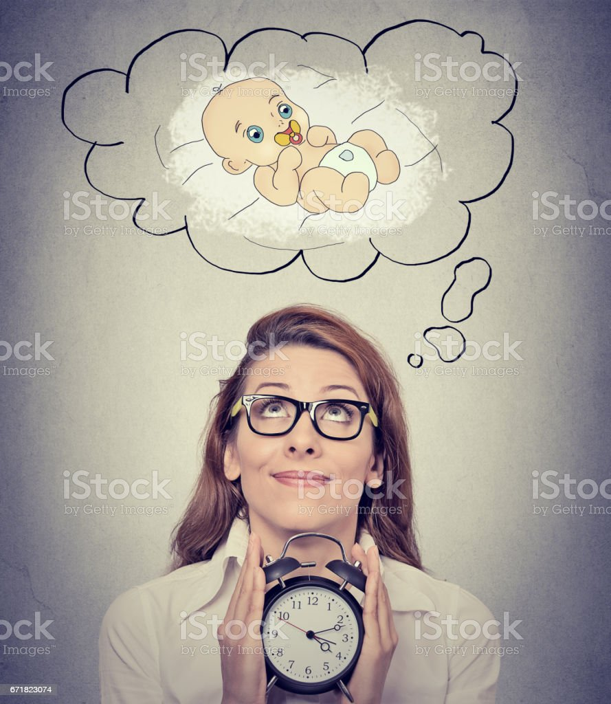 happy woman anticipating a baby looking up holding alarm clock stock photo