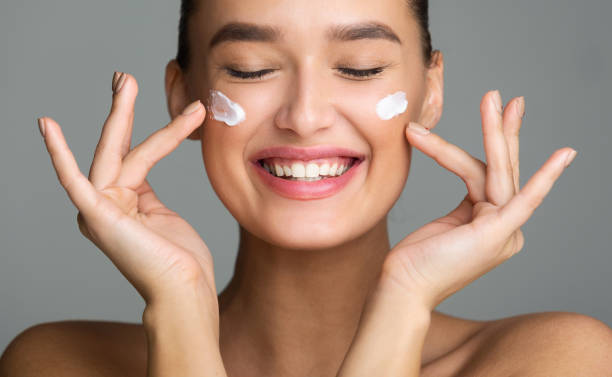gelukkige vrouw toepassing cosmetische crème op haar gezicht - skincare stockfoto's en -beelden