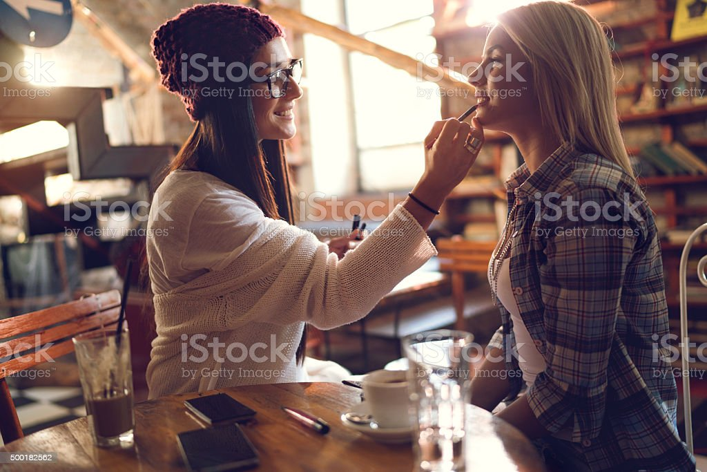 Happy woman applying make-up on her friend's lips. stock photo