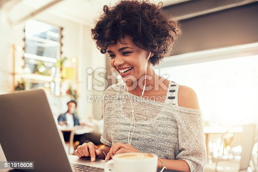 istock Happy woman at cafe using laptop 511918608