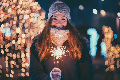 Happy woman at Christmas holding burning sparkler