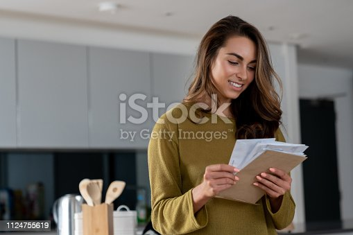 Portrait of a happy woman at home checking her mail and looking happy – lifestyle concepts