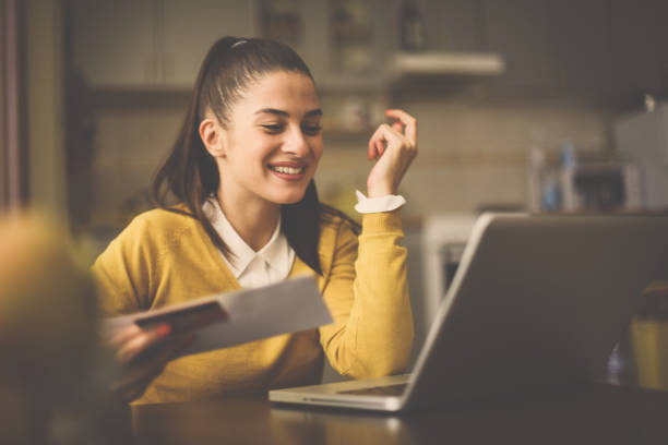 happy woman at home holding credit card and using laptop. - receiving stock photos and pictures