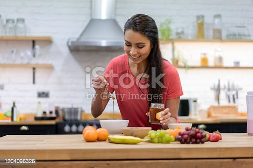 Happy woman at home preparing a healthy breakfast and pouring honey on a parfait - lifestyle concepts