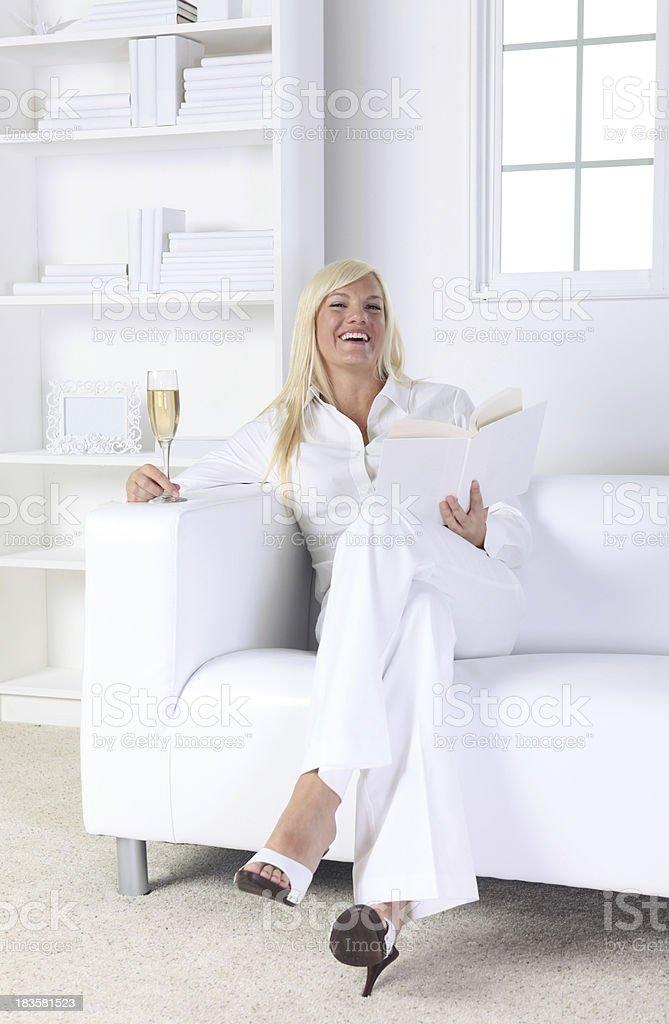 Happy woman at home reading with a glass of wine royalty-free stock photo