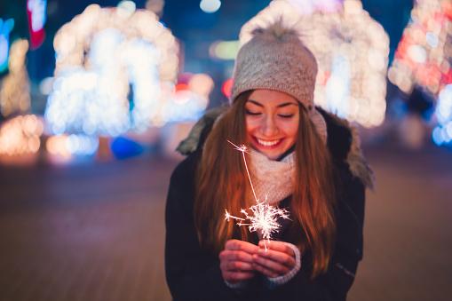 Cute girl holding sparkler and enjoying Christmas outside at night