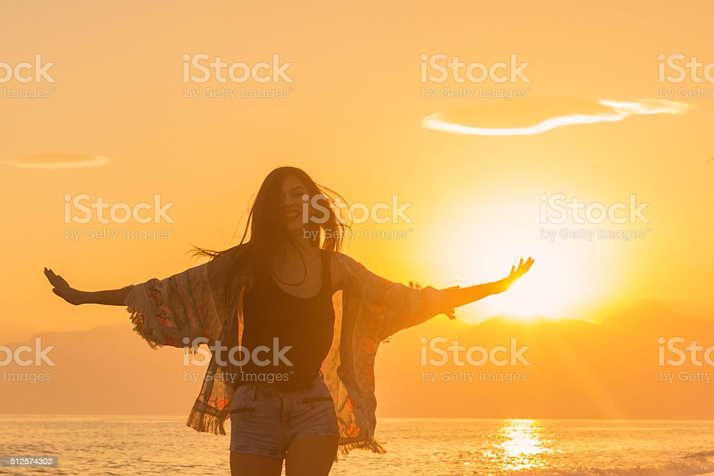 Happy woman at sunset stock photo