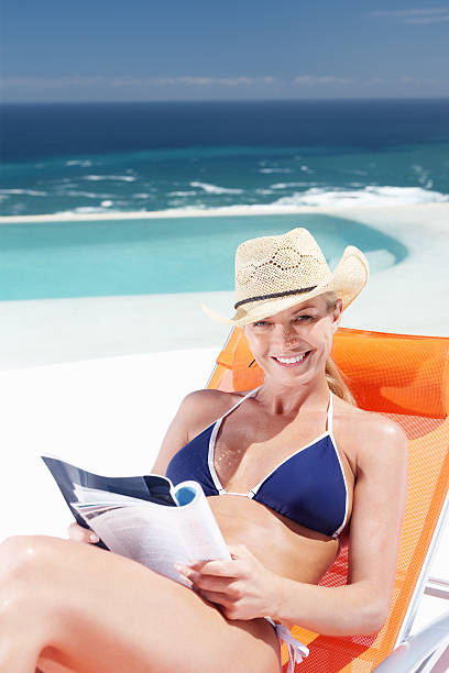 Happy woman at the beach Portrait of smiling mature woman relaxing at the beach reading magazine in lounge chair middle aged women in bikinis stock pictures, royalty-free photos & images