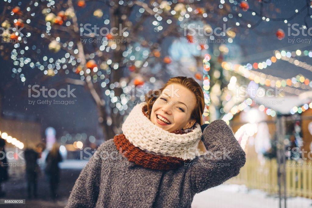 Glückliche Frau auf dem Weihnachtsmarkt in der Nacht – Foto
