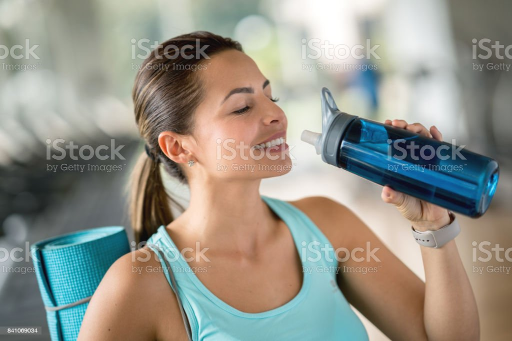 Happy woman at the gym drinking water stock photo istock happy woman at the gym drinking water royalty free stock photo sciox Gallery