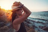 istock Happy woman at the seaside enjoying the sunset 1207089764