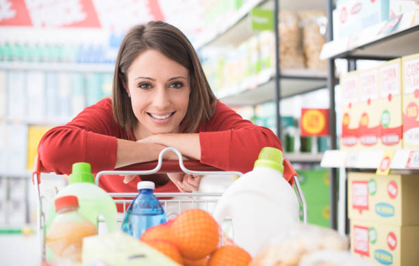 Happy woman at the supermarket Happy woman doing grocery shopping at the supermarket, she is leaning on a full shopping cart, lifestyle and retail concept discount store stock pictures, royalty-free photos & images