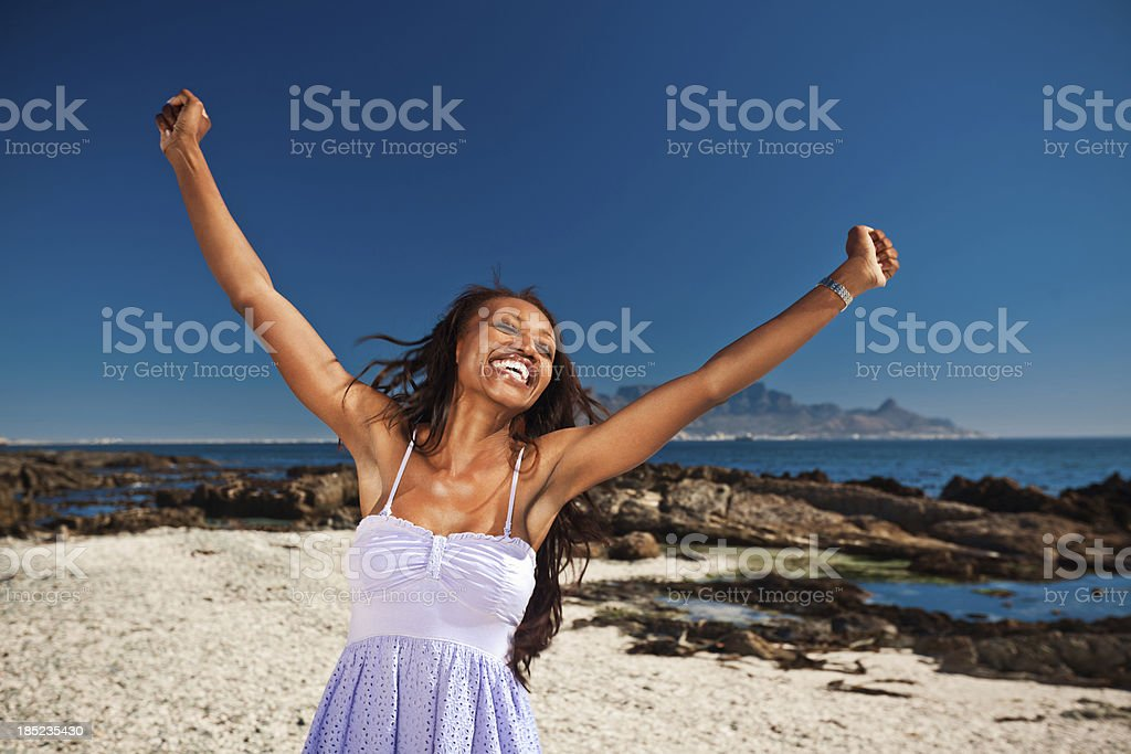 Happy woman at vacation Happy african american woman raising her hands against the Table Mouintain in the background. Adult Stock Photo