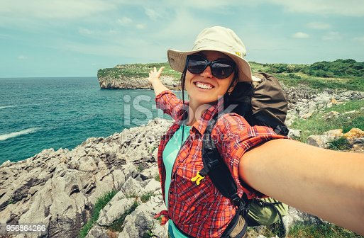 Happy woman backpacker traveler take a selfie photo on amazing ocean coast