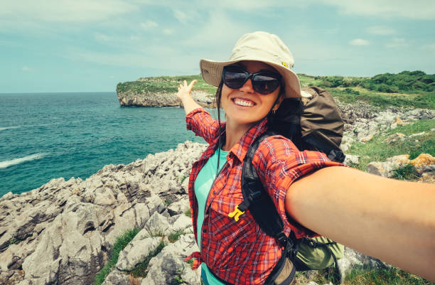 happy woman backpacker traveler take a selfie photo on amazing ocean coast - saccopelista foto e immagini stock