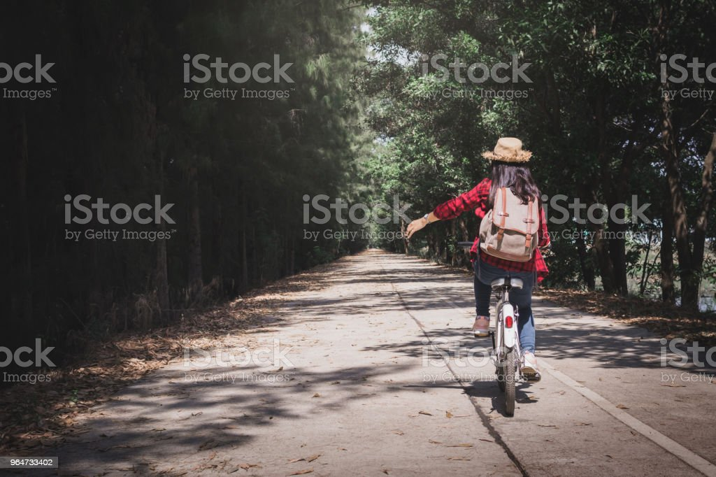 Happy woman backpacker with white bicycle in nature background, Relax time on holiday  travel concept color of hipster style selective and soft focus royalty-free stock photo