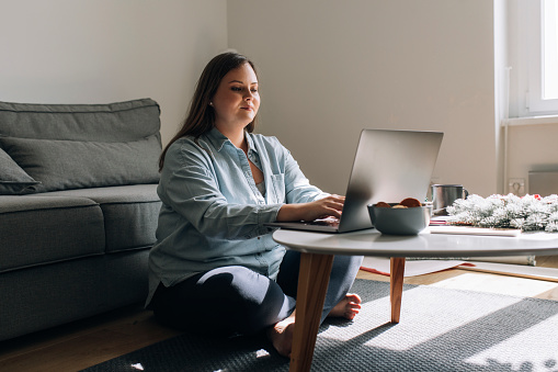 Writing during holiday season: a happy woman sitting on the floor and using her laptop pc.