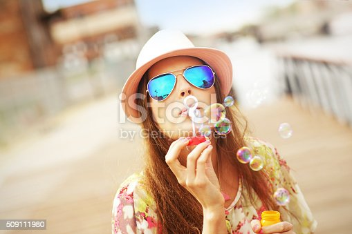 istock Happy woman blowing soap bubbles 509111980