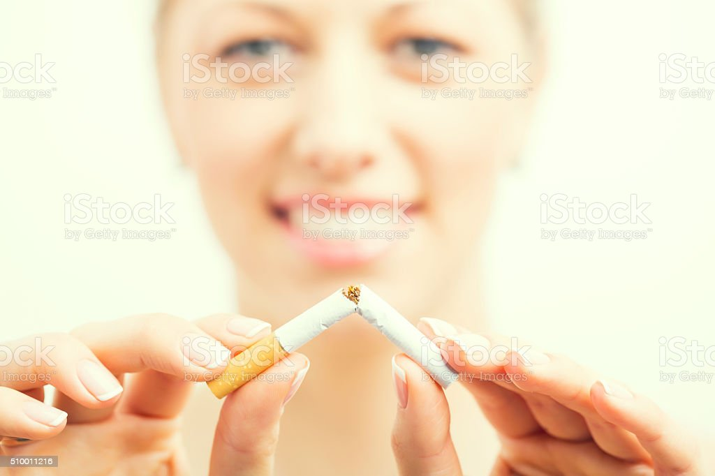 Happy woman breaking cigarette stock photo