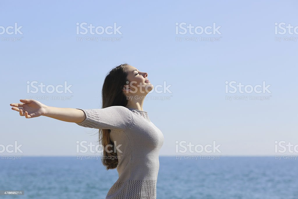 Happy woman breathing deep fresh air and raising arms stock photo