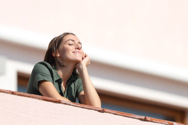 Happy woman breathing fresh air from balcony in apartment stock photo