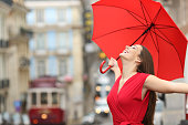 Portrait of a happy woman wearing red blouse under an umbrella breathing in the street of and old town in a rainy day