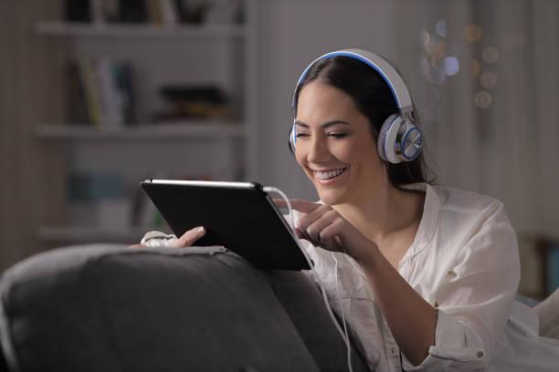 glückliche frau browsing medien in der nacht zu hause - tablet mit displayinhalt stock-fotos und bilder
