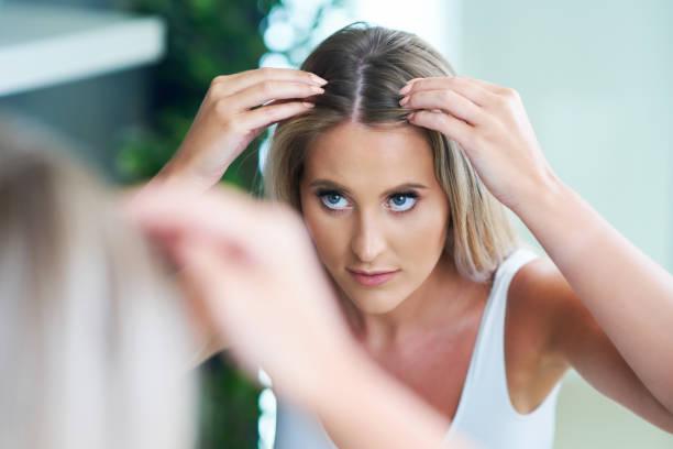 Glückliche Frau bürsten Haare im Badezimmer mit Problem mit Haarausfall – Foto