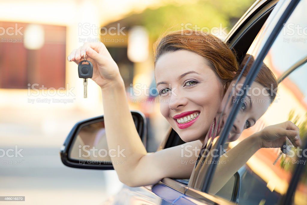 Happy woman, buyer sitting in new car showing keys stock photo