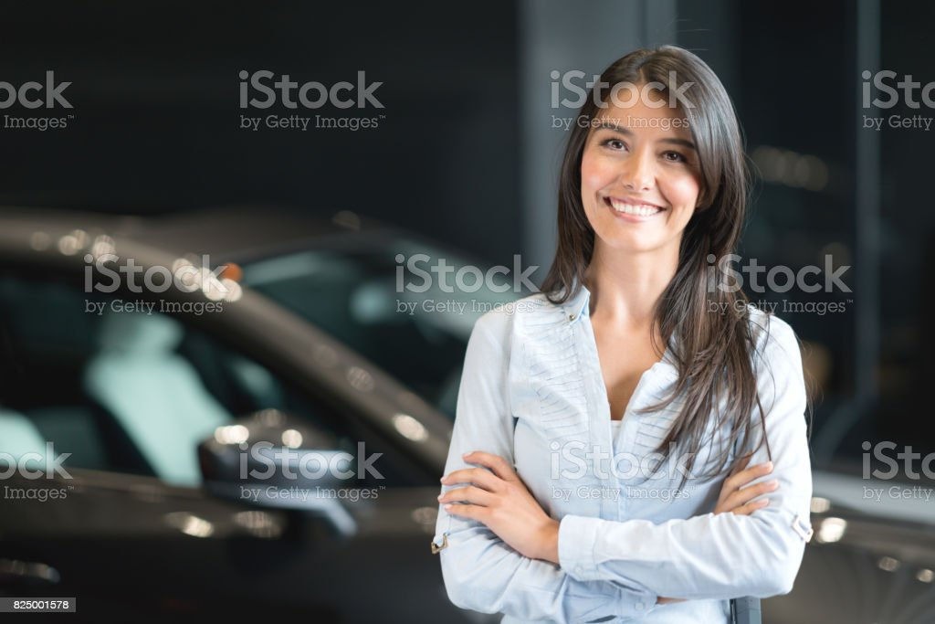 Happy woman buying a car at the dealership stock photo