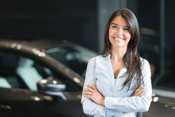 Happy woman buying a car at the dealership Portrait of a happy Latin American woman buying a car at the dealership car salesperson stock pictures, royalty-free photos & images
