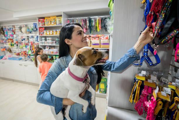 Femme heureuse en achetant une laisse à une animalerie - Photo