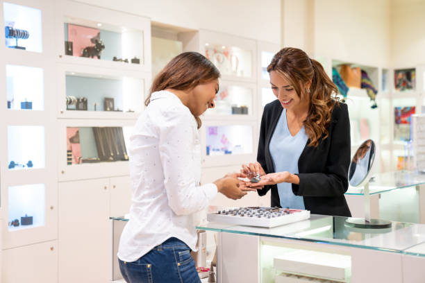 Happy woman buying jewels at a jewelry store Happy woman buying jewels at a jewelry store and talking to the saleswoman over the counter jeweller stock pictures, royalty-free photos & images