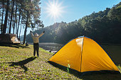 istock Happy woman. Camping and tent under the pine forest in sunset at north of Thailand. 1090966472