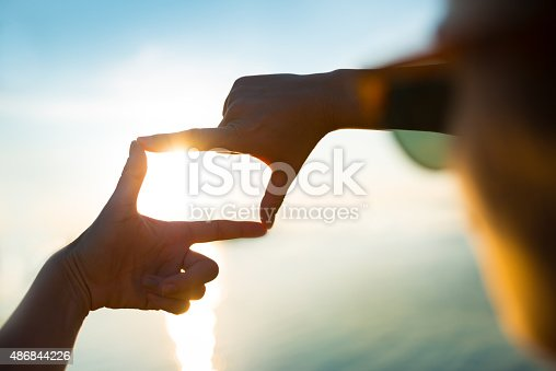 istock happy woman capturing the sunset by the water - Finger Frame 486844226