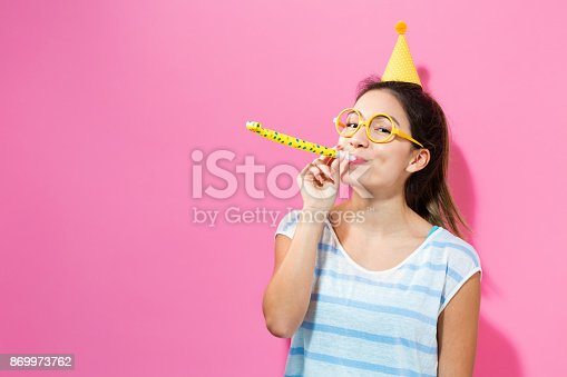 istock Happy woman celebrating with a party hat 869973762