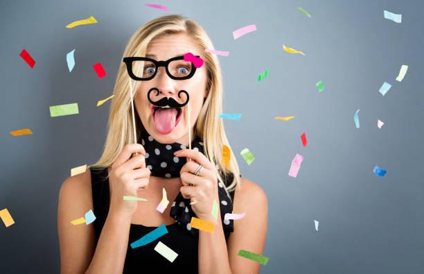 glückliche frau feiert mit konfetti - schnurrbart themenpartys stock-fotos und bilder